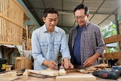 Mature men working with wood. Cheerful mature Vietnamese men discussing size of wooden planks for project stock photography