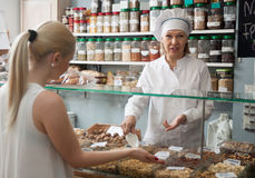 Cheerful mature woman offering client  nuts in local supermarket Stock Photography