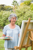 Cheerful mature woman painting on canvas Royalty Free Stock Image