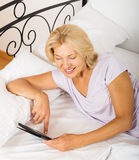 Cheerful  mature woman resting with ereader Royalty Free Stock Photo
