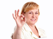 Cheerful mature woman showing the ok sign. Portrait of cheerful mature woman showing the ok sign isolated over white. Shallow depth of field stock photo