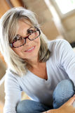 Cheerful mature woman sitting on floor Royalty Free Stock Photos