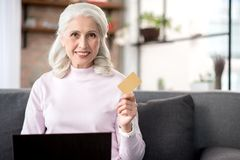 Cheerful mature woman undergoing payment in internet stock image