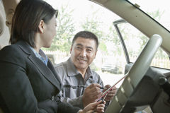 Cheerful Mechanic Explaining to Businesswoman and Showing her the bill Royalty Free Stock Photography