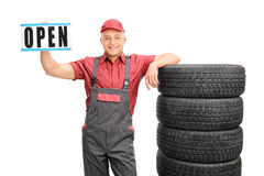 Cheerful mechanic holding an open sign Royalty Free Stock Photo