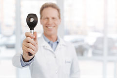 Cheerful medical specialist demonstrating dermatoscope in the clinic. Advising you this useful instrument. Smiling positive upbeat dermatologist enjoying working Stock Image