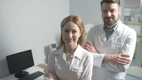 Cheerful medical specialists crossing arms while posing stock video footage