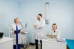 Cheerful medical team in dental office discuss about practice and examining list of patients. royalty free stock photo