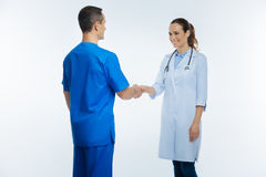 Cheerful medical worker greeting her colleague. Nice to meet you. Cropped shot of a friendly looking young lady looking at her coworker with a cheerful smile on royalty free stock photography