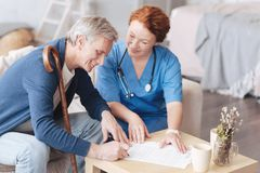 Cheerful medical worker helping patient with insurance application. Supportive attitude. Positive minded doctor smiling while sitting next to her retired patient Royalty Free Stock Image