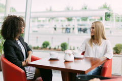 Cheerful meeting of two friends in the cafe. One of them is afro-american. Royalty Free Stock Images