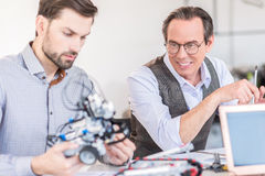 Cheerful men sitting at workplace Stock Image