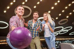 Cheerful men and woman are enjoying kegling game Royalty Free Stock Image