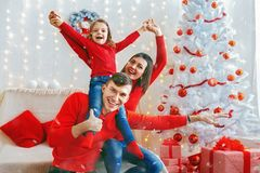 Playful happy family celebrating Christmas. Cheerful men and women with adorable girl posing playfully in sparkles of Christmas adornments Stock Photo