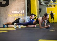 Smiling lady is doing plank with partner indoors Royalty Free Stock Photography