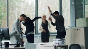 Cheerful men and women are having party in office dancing with papers then throwing them in the air and laughing. Young stock footage