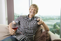 Cheerful mid-adult man with wine glass watching television on sofa at home Royalty Free Stock Photo