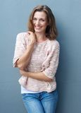 Cheerful mid adult woman smiling in jeans and sweater Stock Image