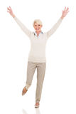 Cheerful mid age woman. Arms up on white background stock photos