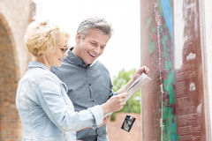 Cheerful middle-aged couple reading map in city Royalty Free Stock Photography