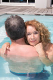 Cheerful middle aged couple spending romantic time by pool Stock Images