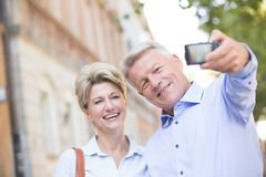 Cheerful middle-aged couple taking self portrait outdoors Royalty Free Stock Image
