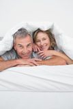 Cheerful middle aged couple under the duvet Stock Images
