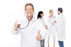 cheerful middle aged doctor with stethoscope showing thumb up while colleagues standing behind stock photo