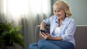 Cheerful middle-aged female sitting on couch and viewing funny photos on phone. Stock photo stock photo