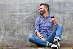 Cheerful middle aged man sitting outside with mobile phone Stock Photo