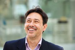 Cheerful middle aged man standing outside and smiling. Close up portrait of cheerful middle aged man standing outside and smiling Stock Image
