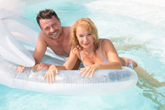 Cheerful midlife couple on holiday in swimming Pool Royalty Free Stock Images