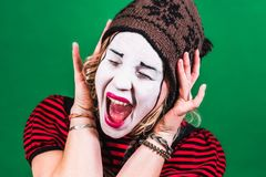 Girl mime posing and grimacing in photo studio Royalty Free Stock Photography