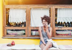 Cheerful mixed girl speaking on the smartphone. Laughing cute Brazilian girl speaking on smartphone while sitting on cushion in front of yellow wall and window royalty free stock photo