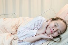 Cheerful  mixed race tween girl in hospital bed Royalty Free Stock Images