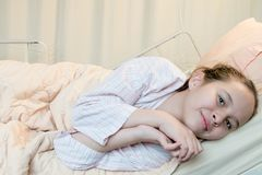 Cheerful  mixed race tween girl in hospital bed Royalty Free Stock Image