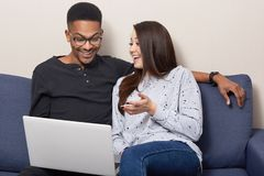 Cheerful mixed race couple use laptop computer for watching movies, sit together on sofa over home interior, browse information, royalty free stock photos