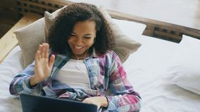 Cheerful mixed race girl having video chat with friends using laptop camera while lying on bed Stock Photography