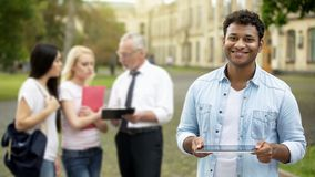 Cheerful mixed-race male holding tablet, using mobile application for education stock image