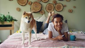 Cheerful mixed race student is watching TV holding remote and pressing buttons choosing television channels while her. Adorable dog is moving on bed at home stock footage