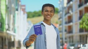 Cheerful mixed-race teen guy showing international passport and smiling, travel. Stock footage stock footage