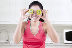 Cheerful model with pieces of kiwi fruit Stock Photo