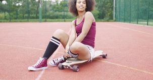 Cheerful model posing on longboard. Pretty and flirty model in casual clothing sitting on longboard while looking at camera on background of basketball sports stock video