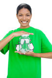 Cheerful model wearing recycling tshirt holding glass pot Stock Photo