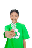 Cheerful model wearing recycling tshirt holding light bulb Royalty Free Stock Image