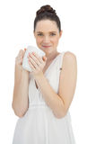 Cheerful model in white dress holding cup of coffee. Posing on white background Royalty Free Stock Photos