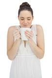 Cheerful model in white dress smelling coffee Stock Image