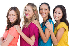 Cheerful models in a line posing with colorful t shirts Royalty Free Stock Photos