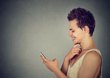 Cheerful modern guy using smart phone smiling royalty free stock images