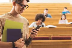 Cheerful modern male student messaging on mobile phone. Outgoing young men is typing message on his smartphone while standing in auditorium. He is holding books Stock Image